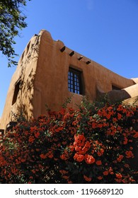 historic abode building and  orange flowers  on a sunny day in the santa fe plaza, santa fe, new mexico