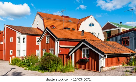 Historic alley with boatswain cabins and vintage houses in Vastervik, Sweden. The alley is covered in gravel. A small garden with flowers and herbs is situated outside the cabin.