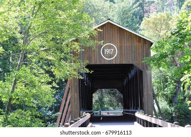 Historic Applegate River Covered Bridge, Medford, Oregon, built in 1917 is surrounded by green trees.