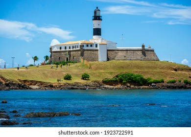 The historic architecture of Salvador in Bahia, Brazil showcasing the Farol da Barra Lighthouse at Bahia de Todos os Santos Bay on a sunny summer day