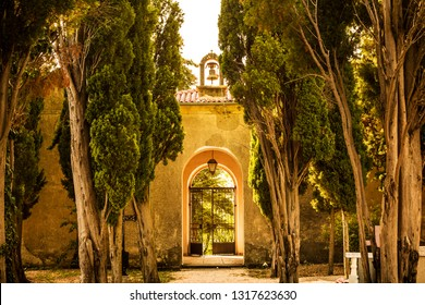Historic archway (gate with a bell), wall and old cypress trees. Calm summer countryside landscape - architecture and nature.