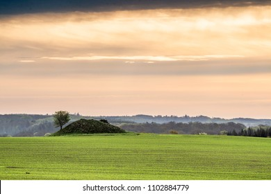 Historic barrow hill on a green field in Denmark in a cloudy sunrise