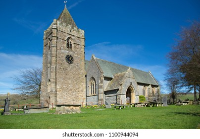 Historic beautiful Norman church in the village of Thornton in Lonsdale in the North Yorkshire Dales in England UK with churchyard in sunny weather with blue skies and clouds