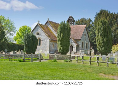 Historic beautiful Norman church in the village of Itchen Abbas on the banks of the river Itchen in Hampshire in England UK with churchyard in sunny weather with blue skies and clouds