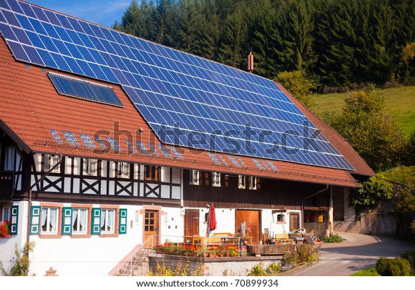 Historic Black Forest (Germany) farm house with modern solar panels on large roof.