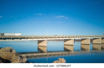 Historic blue and white arch truss bridge over the Columbia River with blue skies and clouds on a sunny morning in Kennewick-Pasco Washington