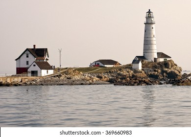 Historic Boston Harbor lighthouse is a popular summertime attraction, especially in the early evening when the sun sets, creating a warm glow.