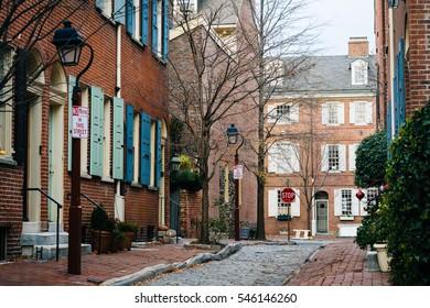 Historic brick houses and narrow cobblestone alley in Society Hill, Philadelphia, Pennsylvania.