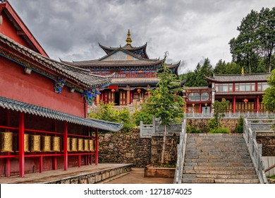 Historic Buddhist Temple Complex on Hilltop with Row of Gold Tibetan Prayer Wheels in Traditional Village of Baisha, Yunnan, China.