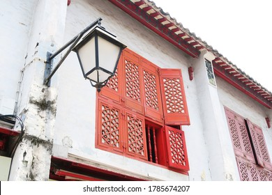 Historic building with red window and grey wall in R. da Felicidade