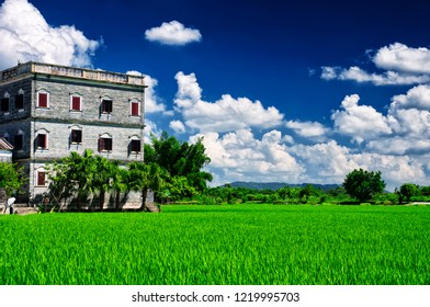 A historic building and rice field of Kaiping Diaolou in Zili village in Kaiping China in Guangdong province on a sunny blue sky day.