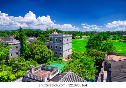The historic buildings and a rice paddy at Kaiping Diaolou in Zili village in Kaiping China in Guangdong province on a sunny blue sky day.