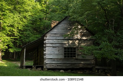 A historic cabin is surrounded by woods in the Smoky Mountain National Park.