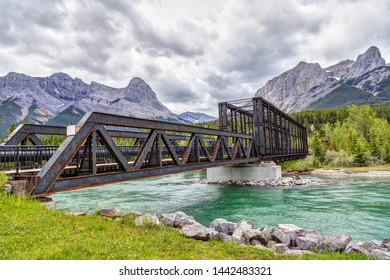 Historic Canmore Engine Bridge over the Bow River in the Canadian Rockies with Ha Ling Peak and Mt Rundle in the background. The railway bridge was built in 1891 but is now the Bow River hiking loop.