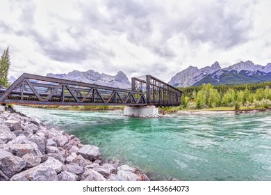 Historic Canmore Engine Bridge over the Bow River in the Canadian Rockies with Ha Ling Peak and Mt Rundle in the background. The railway bridge was built in 189 but is now the Bow River hiking loop.