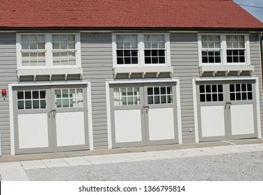 Historic caretaker garage with red shingle roof and three garage doors with double hung windows over them. Garage bypass doors have decorative corbels overhead.