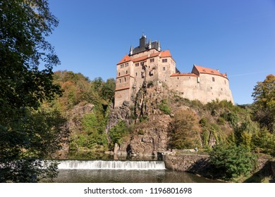 Historic castle named Kriebstein with waterfall in the foreground, Saxony, Germany
