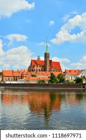A historic church building on the banks of the river in Wrocław.