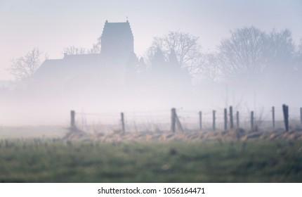 Historic church in misty dutch rural landscape. Geesteren, Achterhoek, Gelderland.