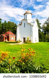 Historic church of the Nativity of the Theotokos (1226) with colorful flowers on foregroundon on Peryn Skete in Veliky Novgorod, Russia