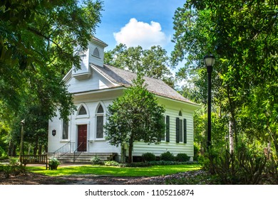 Historic church in Wilmington North Carolina. Located in Airlie Gardens, this white painted church building sits amids the green mature oaks on a manicured green lawn. Gardeners and Tourists enjoy.