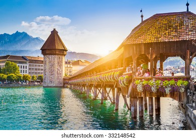 Historic city center of Lucerne with famous Chapel Bridge and Mount Pilatus summit in the background in golden evening light at sunset with blue sky and clouds, Canton of Lucerne, Switzerland