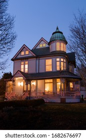 Historic classic Queen Anne Victorian house at dusk in the Indianapolis, Old Northside neighborhood