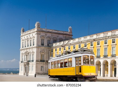 historic classic yellow tram of Lisbon built partially of wood in front of Lisbon central square Praca de Comercio, Portugal