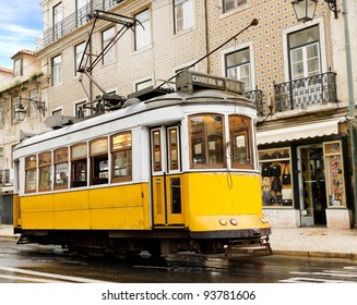 historic classic yellow tram of Lisbon built partially of wood navigating, narrow, winding streets, Portugal
