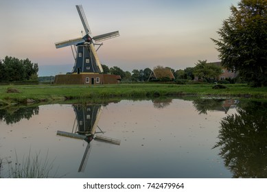 Historic corn mill called The Bataaf in Winterswijk in the evening reflecting in the nearby pond