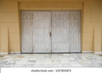 Historic door in an old building. Gray shabby front door.