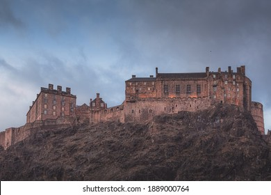The historic Edinburgh Castle perched atop Castlehill against a moody backdrop on a winter's evening.