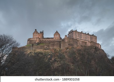 The historic Edinburgh Castle perched atop Castlehill against a moody backdrop on a dark evening in Scotland.