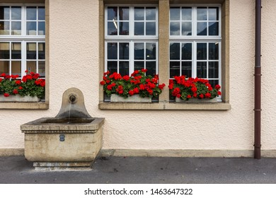 Historic European style wall and windows with flower bed and fountain in Interlaken, Switzerland.