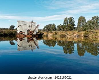 Historic Gold Dredge left abandoned on lake with mirror reflections.  Eldorado, Victoria,  Australia.