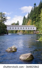 The historic Goodpasture covered bridge outside of Eugene, Oregon, under brilliant blue early fall sky.