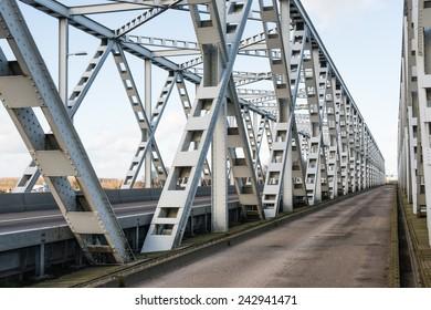 Historic gray painted Dutch riveted truss bridge against a blue sky.