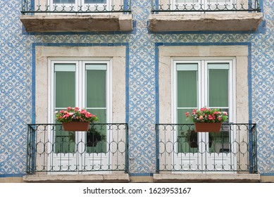 historic house facade with blue azulejos, two french balconies and geranium flower boxes, lisbon portugal