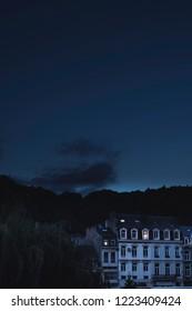 Historic houses with illuminated windows in dusk.