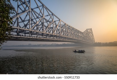 Historic Howrah bridge on  Ganga river on a misty winter morning with a wooden fishing boat passing the bridge. Kolkata, India.