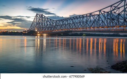 Historic Howrah bridge on the river Hooghly after sunset with city light reflections.