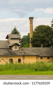 Historic Hungarian rural distillery. High chimney with a stork's nest. Historic country industrial building with grass and trees. Close up. Lower Austria. Burgenland. Central Europe.
