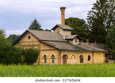 Historic Hungarian rural distillery. High chimney with a stork's nest. Historic country industrial building with grass and trees. Lower Austria. Burgenland. Central Europe.