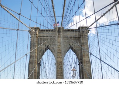 The historic and iconic brick tower and high-tension wire cables of the Brooklyn Bridge in New York City.