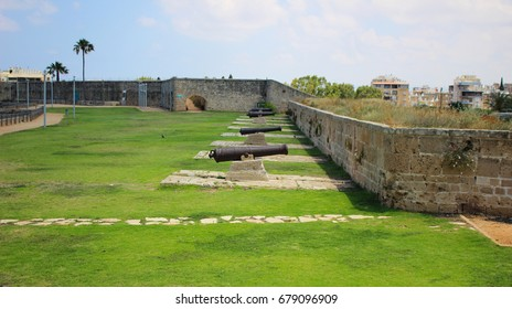 Historic imperial cannons in a park facing a citadel's wall in the Old City of Akko (Acre), Israel