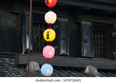 """Historic Japanese house in Kawagoe in Saitama prefecture in Japan and colorful lanterns. Translation of Japanese letter on the lanterns: """"Kawagoe 1st Avenue""""."""