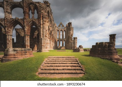 The historic landmark 7th century ruins of Whitby Abbey perched atop East Cliff north Yorkshire, England with a dark, moody sky.