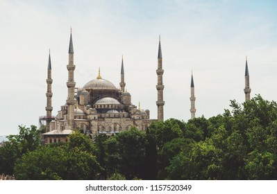 Historic Landmark Sultanahmet Mosque in Istanbul. Exterior view of the mosque and minarets. Beautiful scenery with a view of the mosque, a blue summer sky with clouds and birds.
