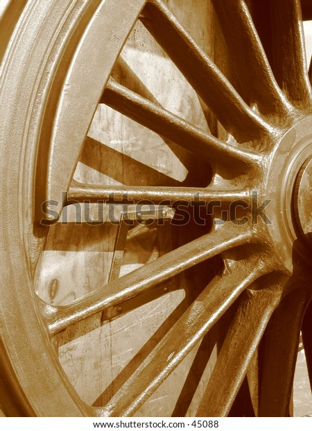 Historic locomotive wheel in sepia tone.