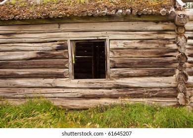 Historic log house, wall with glassless window frame and earth roof.